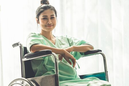 Happy patient smile while sitting on wheelchair after recovery from injury at the hospital ward. Medical healthcare and good patient service concept.