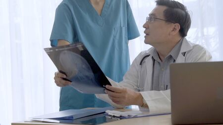 Doctor and nurse discuss on surgery result showing on x-ray film image of patient head. Concept of medical healthcare and specialist doctor staff service.