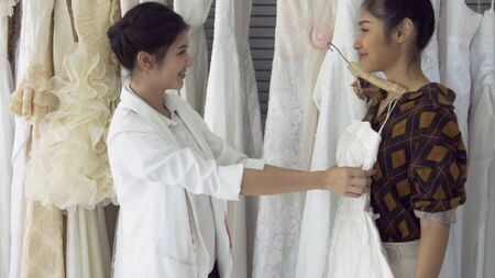 Future bride customer talking with wedding store shopkeeper to buy wedding dress and accessories for her upcoming wedding ceremony. Stock Photo