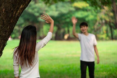 Junge Leute, Mann und Frau grüßen oder verabschieden sich, indem sie die Hände im Park winken.