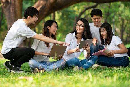 Equipo de jóvenes estudiantes que estudian en un proyecto grupal en el parque de la universidad o la escuela. Aprendizaje feliz, trabajo en equipo comunitario y concepto de amistad juvenil. Foto de archivo