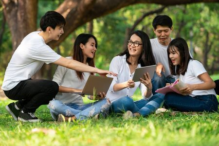 Team of young students studying in a group project in the park of university or school. Happy learning, community teamwork and youth friendship concept. Reklamní fotografie