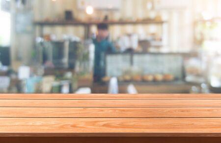 Tavolo in legno sullo sfondo sfocato della moderna sala ristorante o caffetteria con copia spazio vuoto sul tavolo per il modello di visualizzazione del prodotto. Concetto di design del bancone del ristorante interno.