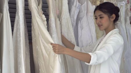 Future bride choosing wedding dress for her upcoming wedding ceremony at the wedding shop. Stock Photo