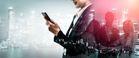 Imagen de doble exposición del concepto de tecnología de red de comunicación empresarial - gente de negocios que usa un teléfono inteligente o dispositivo de teléfono móvil en el fondo del paisaje urbano moderno. Foto de archivo