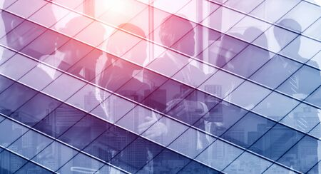 Double exposure image of faded business abstract background with office building and people conference group meeting showing partnership success of business deal. 写真素材