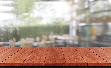 Wood table in blurry background of modern restaurant room or coffee shop with empty copy space on the table for product display mockup. Interior restaurant counter design concept. Stock Photo