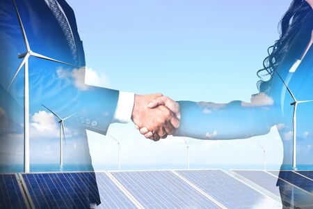 Double exposure graphic of business people handshake over wind turbine farm and green renewable energy worker interface. Concept of sustainability development by alternative energy. Archivio Fotografico