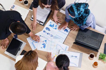 ラップトップコンピュータ、コーヒー、テーブル上の文書を備えた現代オフィスの他のビジネスマンやビジネスウーマンとのグループミーティングにおけるビジネスマンエグゼクティブのトップビュー。企業のビジネスチームのコンセプト。 写真素材