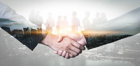 Image à double exposition de la poignée de main des hommes d'affaires sur l'immeuble de bureaux de la ville en arrière-plan montrant le succès du partenariat de l'accord commercial. Concept de travail d'équipe d'entreprise, de partenaire de confiance et d'accord de travail. Banque d'images