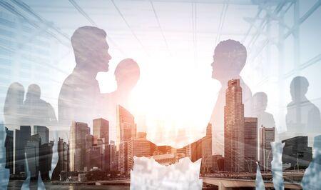 Imagen de doble exposición de la reunión del grupo de conferencia de muchos empresarios en el edificio de oficinas de la ciudad en segundo plano que muestra el éxito de la asociación del trato comercial. Concepto de trabajo en equipo, confianza y acuerdo.