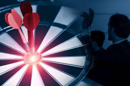 Geschäftszielziel für das Erfolgsstrategiekonzept - Roter Pfeil, der das Zentrumsziel auf der Dartscheibe trifft, mit Geschäftsleuten, die im Hintergrund arbeiten und Präzision und Erfolg des Geschäftsziels zeigen.
