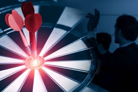 Objectif commercial pour le concept de stratégie de réussite - Flèche de fléchette rouge frappant l'objectif central sur le jeu de fléchettes avec des hommes d'affaires travaillant en arrière-plan montrant la précision et le succès de la cible commerciale.