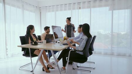 Senior Leader, der Teammitgliedern Ratschläge gibt. Kreative Geschäftsleute treffen sich am Tisch im modernen Büro. Multikulturelles Geschäftsteam.
