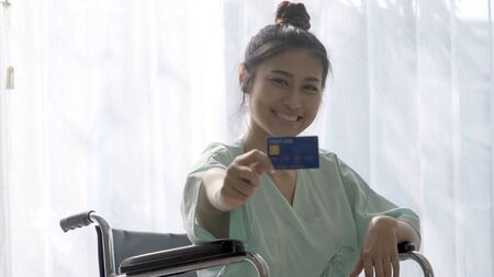 Happy patient hold credit card and smile while sitting on wheelchair after recovery from injury at the hospital ward. Medical healthcare and good patient money payment service concept.