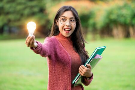 Creative young woman hold shinning light bulb. Concept of knowledge, intelligence and inspiration.