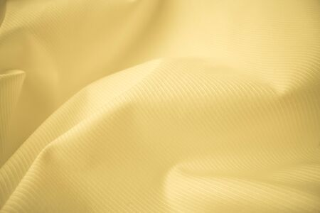 Shiny flowing cloth texture in macro shot. Wavy clean silk weave material. Textile abstract background. 免版税图像