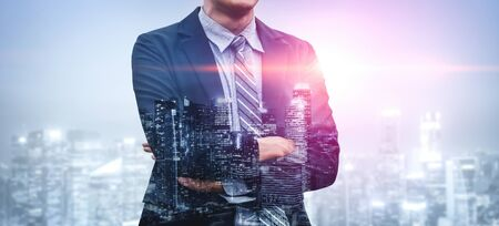 Double Exposure Image of Business Person on modern city background. Future business and communication technology concept. Surreal futuristic cityscape and abstract multiple exposure graphic interface. Stock Photo
