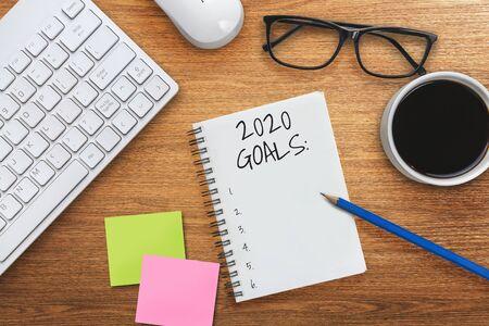 Lista de objetivos de resolución de año nuevo 2020: escritorio de oficina comercial con cuaderno escrito a mano sobre la lista del plan de establecimiento de objetivos y resoluciones de año nuevo. Concepto de cambio y determinación. Foto de archivo
