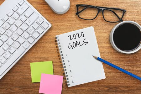 New Year Resolution Goal List 2020 - Business office desk with notebook written in handwriting about plan listing of new year goals and resolutions setting. Change and determination concept. 免版税图像 - 133535055