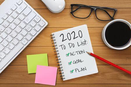 Neujahrsauflösungszielliste 2020 - Geschäftsschreibtisch mit handschriftlich geschriebenem Notizbuch über die Planliste der Neujahrsziele und -vorsätze. Änderungs- und Bestimmungskonzept.