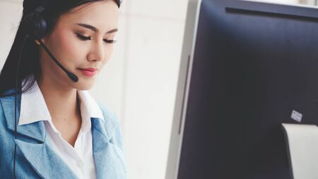 Customer support agent or call center with headset works on desktop computer while supporting the customer on phone call. Operator service business representative concept.