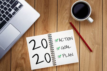 New Year Resolution Goal List 2020 - Business office desk with notebook written in handwriting about plan listing of new year goals and resolutions setting. Change and determination concept.