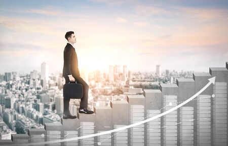 Business man climbing up stair steps to career success with business district and horizon skyline as background. Concept of business goal success, growth of career path and starting up a new business. Reklamní fotografie