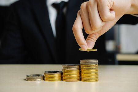 Geschäftsmann, der mit Münzgeldwährung arbeitet. Konzept des Investitionswachstums und der Geldeinsparung.