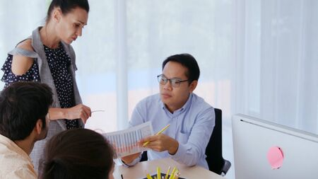 Unhappy business people in group meeting in office. The team is frustrated because of project failure. Business problem and crisis concept. Stock Photo