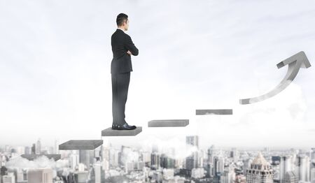 Business man climbing up stair steps to career success with business district and horizon skyline as background. Concept of business goal success, growth of career path and starting up a new business. Stock fotó