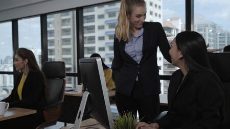 Young leader gives advice to young woman worker in modern office. Leadership and training concept.