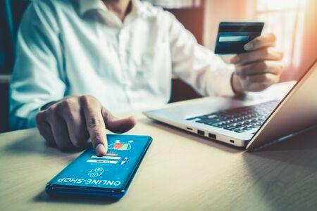 Junger Mann verwendet Kreditkarte für Online-Shopping-Zahlungen auf Laptop-Computer-Anwendung oder Website. E-Commerce- und Online-Shopping-Konzept.