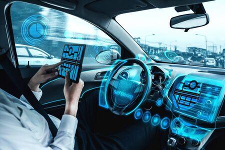 Selbstfahrendes autonomes Auto mit entspanntem jungen Mann, der auf dem Fahrersitz sitzt, fährt auf der belebten Autobahn in der Stadt. Konzept des maschinellen Lernens, der künstlichen Intelligenz und der erweiterten Realität.