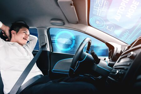 Self-driving autonomous car with relaxed young man sitting at driver seat is driving on busy highway road in the city. Concept of machine learning, artificial intelligence and augmented reality. Reklamní fotografie
