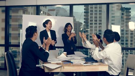 Successful Asian businessman and businesswoman celebrate project success while attending a group meeting. Victory and winner concept. 스톡 콘텐츠