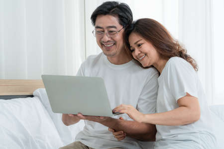 Happy Asian senior couple having good time at home. Old people retirement and healthy citizens elderly concept. 写真素材
