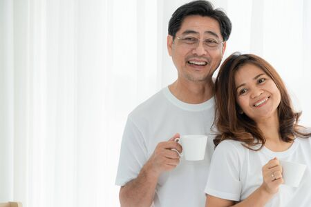 Happy Asian senior couple having good time at home. Old people retirement and healthy citizens elderly concept.