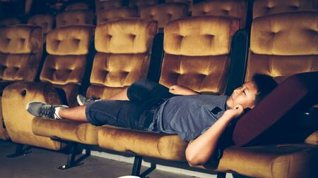 A boy laying down on the armchair and enjoy watching movie in cinema.