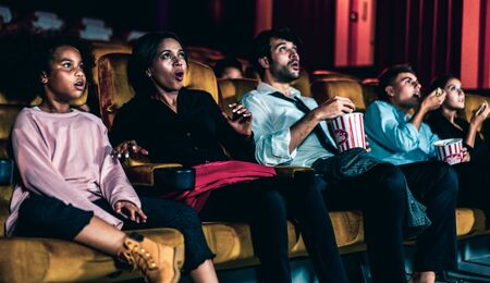 Shocked audience watching a horror movie in the cinema