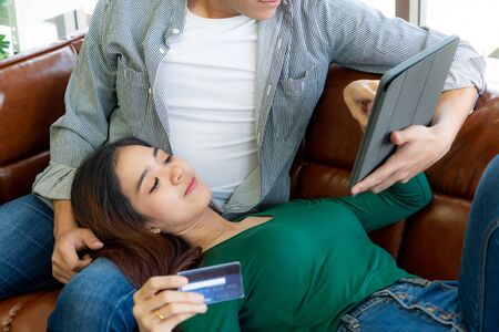 Young couple use credit card for online shopping on internet website at home. Number on the credit card is mock up. No personal information shown on the credit card. Online business shopping concept. Stock Photo