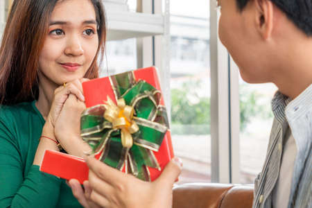 Happy couple giving gift present to celebrate anniversary. Marriage lifestyle, love and relationship concept.