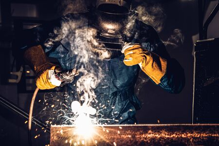 Metal welder working with arc welding machine to weld steel at factory while wearing safety equipment. Metalwork manufacturing and construction maintenance service by manual skill labor concept.