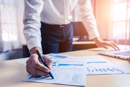 Businessman accountant or financial expert analyze business report graph and finance chart at corporate office. Concept of finance economy, banking business and stock market research. Фото со стока