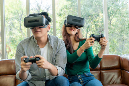 Young happy Asian couple playing video games in living room. Cheerful people having fun with computer gaming concept.