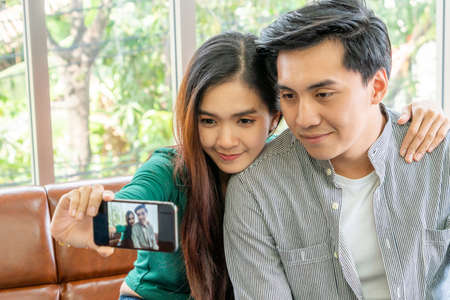 Happy Asian couple enjoy taking selfie photo with mobile phone in living room at home.