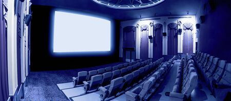 Cinema theater screen in front of seat rows in movie theater showing white screen projected from cinematograph. The cinema theater is decorated in classical style for luxury feeling of movie watching. Imagens