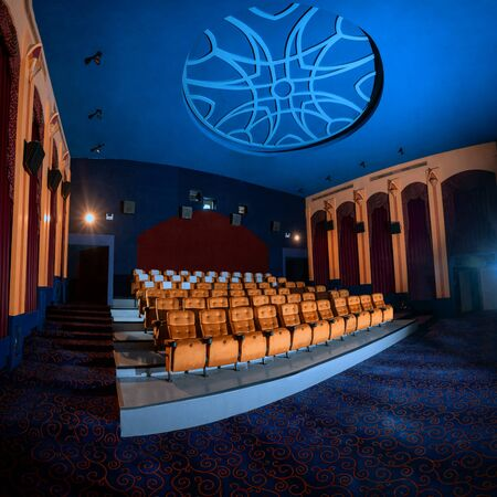 Large cinema theater interior with seat rows for audience to sit in movie theater premiere by cinematograph projector. The cinema theater is decorated in classical for luxury feel of movie watching.