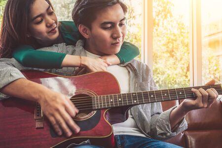 Junges asiatisches Paar spielt Gitarre und singt im Wohnzimmer zu Hause zusammen. Musik- und Lifestyle-Konzept.