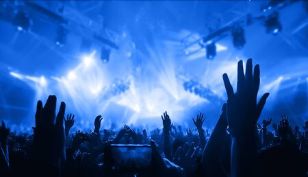 Happy people dance in nightclub DJ party concert and listen to electronic dancing music from DJ on the stage. Silhouette cheerful crowd celebrate New Year party 2020. People lifestyle DJ nightlife. Stock Photo